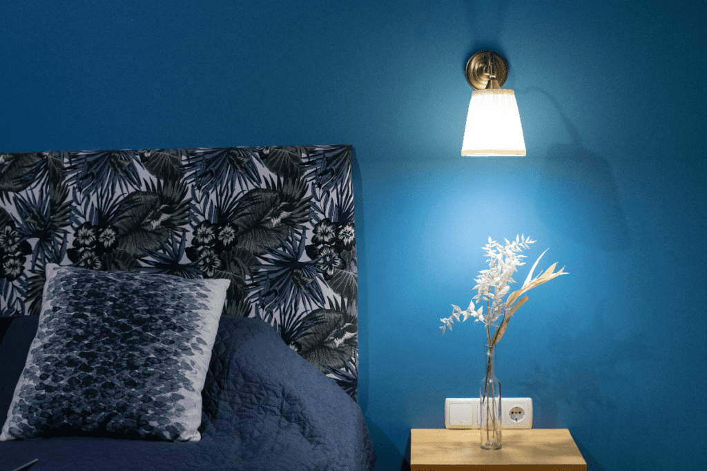 Cobalt colored bedroom wall with wall light next to headboard and above nightstand.