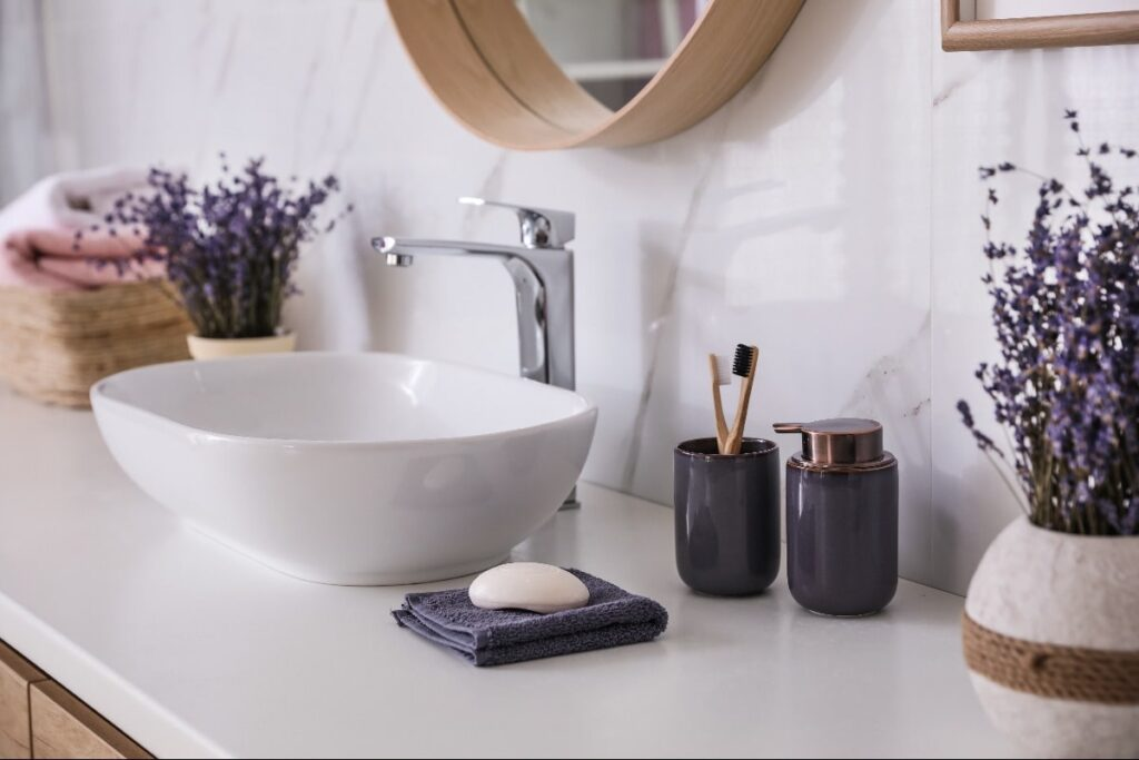 Bathroom vanity with purple accessorie sincluding lavendar plants in flower pot, purple toothbrush holder, soap dispenser, and hand towels.