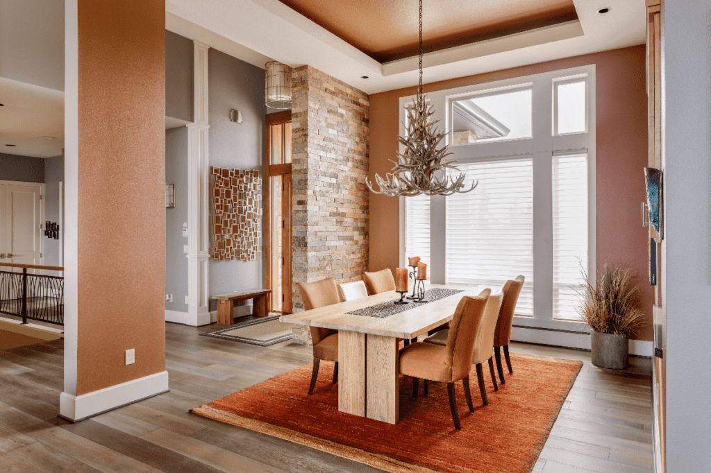Dining room with amber color theme and orange rug under dining table.