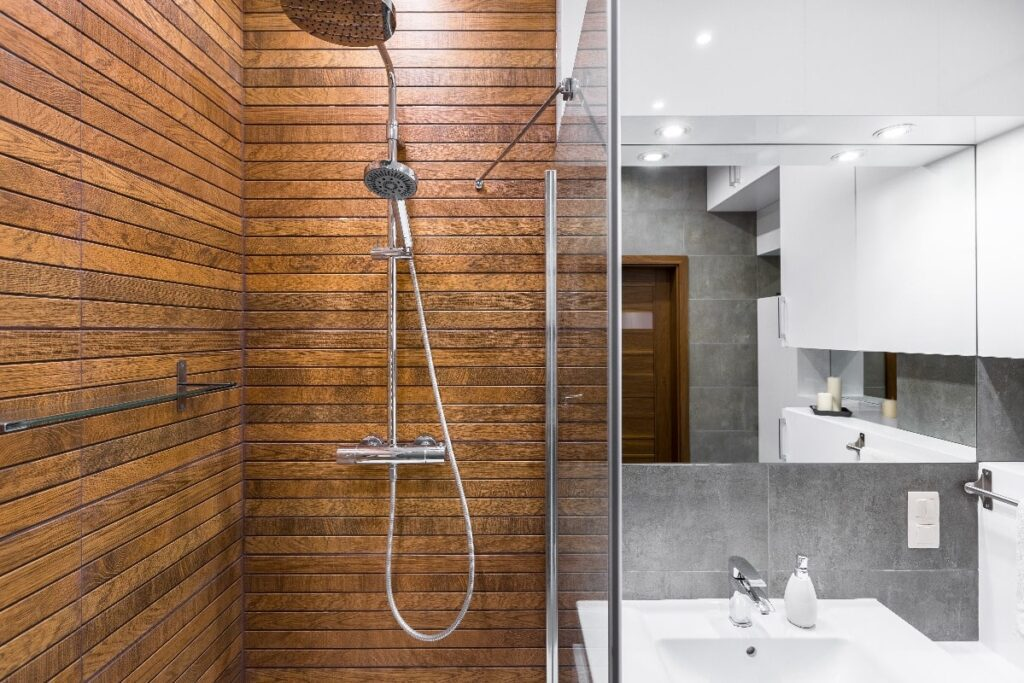 Bathroom view of wooden shower and shower faucet.