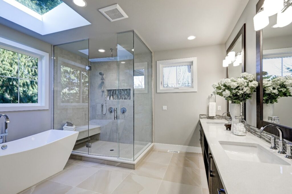 View of entire bathroom highlighting  ceiling lights and vanity lights. All lights are turned on.