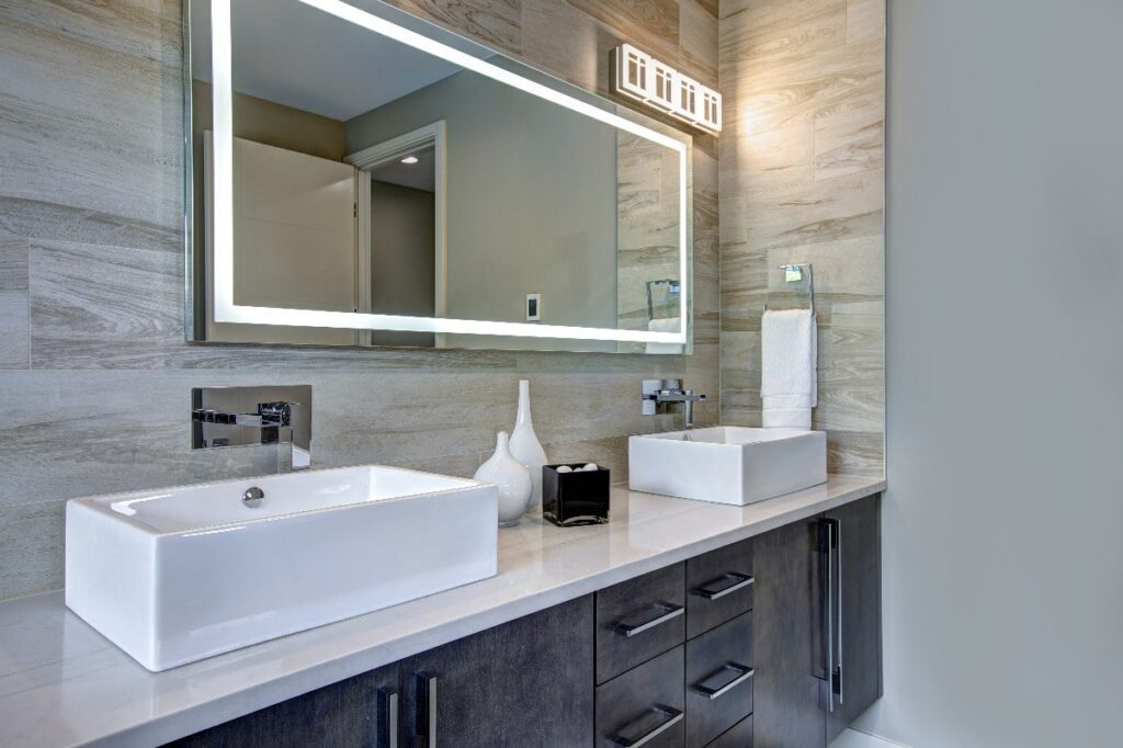 Lighted mirror above bathroom vanity with double sinks.